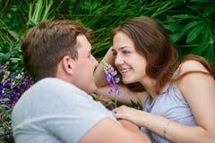 Couples dans l'amour se situant dans l'herbe sur un pré d'été Photos libres de droits