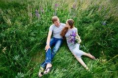 Couples dans l'amour se situant dans l'herbe sur un pré d'été Images libres de droits