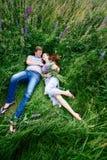 Couples dans l'amour se situant dans l'herbe sur un pré d'été Photo stock