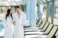 Couples dans l'amour se tenant à côté d'une piscine dans une robe longue Image stock
