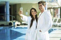 Couples dans l'amour se tenant à côté d'une piscine dans une robe longue Photo stock