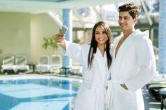 Couples dans l'amour se tenant à côté d'une piscine dans une robe longue Image libre de droits