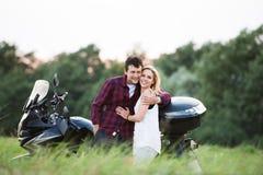 Couples dans l'amour se tenant à une motocyclette Nature verte Image libre de droits