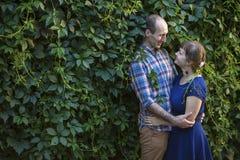 Couples dans l'amour se tenant dehors sur le fond vert Amour Photographie stock