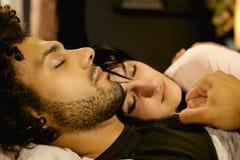Couples dans l'amour se tenant tout en dormant la nuit dans la femme de lit hors focale Photos libres de droits