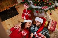 Couples dans l'amour se trouvant sous l'arbre de Noël Photo libre de droits