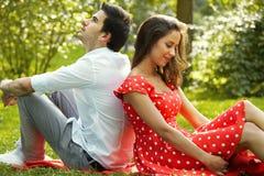 Couples dans l'amour se trouvant sur l'herbe en parc Photos stock