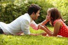 Couples dans l'amour se trouvant sur l'herbe en parc Images libres de droits