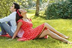 Couples dans l'amour se trouvant sur l'herbe en parc Photo libre de droits