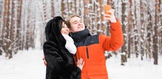 Couples dans l'amour souriant et faisant le selfie en hiver dehors Photos libres de droits