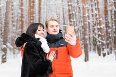 Couples dans l'amour souriant et faisant le selfie en hiver dehors Photo libre de droits