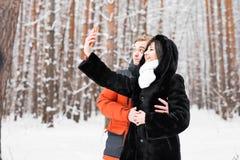 Couples dans l'amour souriant et faisant le selfie en hiver dehors Images libres de droits
