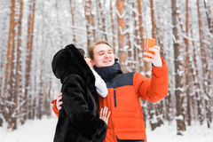 Couples dans l'amour souriant et faisant le selfie en hiver dehors Photographie stock libre de droits