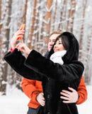 Couples dans l'amour souriant et faisant le selfie en hiver dehors Photographie stock