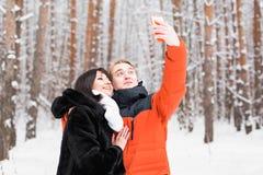 Couples dans l'amour souriant et faisant le selfie en hiver dehors Images stock