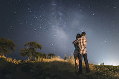 Couples dans l'amour sous des étoiles de galaxie de manière laiteuse Photos stock