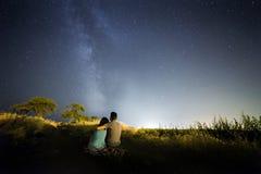Couples dans l'amour sous des étoiles de galaxie de manière laiteuse Photographie stock libre de droits