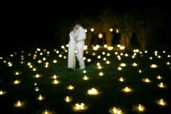 Couples dans l'amour sur l'herbe avec des bougies au nigth Photographie stock
