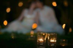 Couples dans l'amour sur l'herbe avec des bougies au nigth Images stock