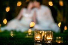 Couples dans l'amour sur l'herbe avec des bougies au nigth de yje Photographie stock