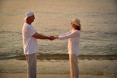Couples dans l'amour sur la plage sablonneuse dans le coucher du soleil Photos libres de droits