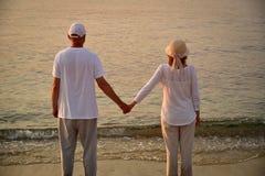 Couples dans l'amour sur la plage sablonneuse dans le coucher du soleil Photo libre de droits