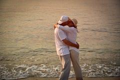 Couples dans l'amour sur la plage sablonneuse dans le coucher du soleil Image stock