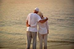Couples dans l'amour sur la plage sablonneuse dans le coucher du soleil Images libres de droits