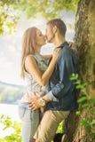 Couples dans l'amour sur le lac, sous les arbres, embrassant Photographie stock libre de droits