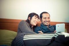 Couples dans l'amour sur le lit utilisant le comprimé Photos libres de droits