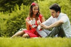 Couples dans l'amour sur le pique-nique en parc Photographie stock