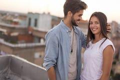 Couples dans l'amour sur un dessus de toit de bâtiment au coucher du soleil image libre de droits