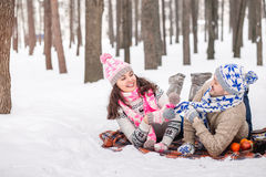 Couples dans l'amour sur une couverture jouant en hiver dehors Photos stock