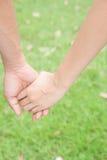 Couples dans l'amour tenant des mains, le betwee d'amitié et de concept d'amour Photos stock