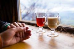 Couples dans l'amour tenant des mains, les couples buvant du café chaud et Photos libres de droits