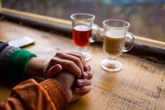 Couples dans l'amour tenant des mains, les couples buvant du café chaud et Images stock