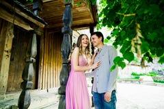 Couples dans l'amour tenant la maison proche Mur en bois rustique Images libres de droits