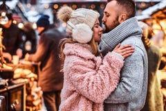 Couples dans l'amour, un couple élégant portant les vêtements chauds caressant ensemble et se regardant la foire d'hiver a images libres de droits