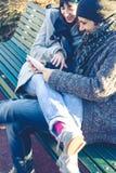 Couples dans l'amour utilisant le comprimé au parc Photos stock