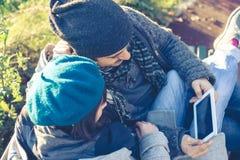 Couples dans l'amour utilisant le comprimé au parc Photo libre de droits