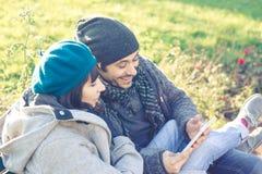 Couples dans l'amour utilisant le comprimé au parc Images libres de droits