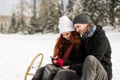 Couples dans l'amour utilisant le mobile tout en se reposant sur le traîneau Photos libres de droits