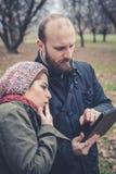 Couples dans l'amour utilisant le wifi se reliant de radio de Web de comprimé Images stock