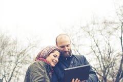Couples dans l'amour utilisant le wifi se reliant de radio de Web de comprimé Images libres de droits