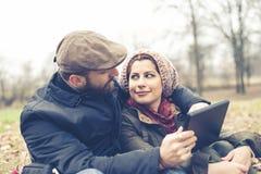 Couples dans l'amour utilisant le wifi se reliant de radio de Web de comprimé Photographie stock