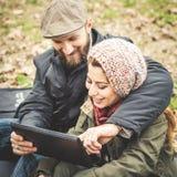 Couples dans l'amour utilisant le wifi se reliant de radio de Web de comprimé Photos libres de droits