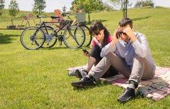 Couples dans l'amour utilisant smartphones sur le parc Photos stock
