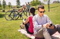 Couples dans l'amour utilisant smartphones sur le parc Photo stock