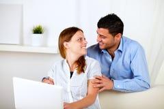 Couples dans l'amour utilisant un ordinateur portatif à la maison Image libre de droits