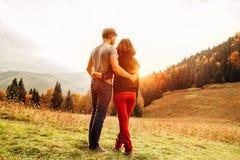 Couples dans l'eeach énorme d'offre d'amour autre sur le pré de coucher du soleil Photos libres de droits